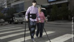 Image: A man is wearing the indego exoskeleton, crossing a crosswalk; Copyright: Parker Hannifin Corporation