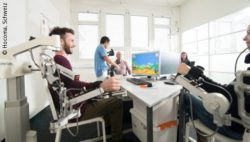 Image: Several people use the Armeo system and playing a videogame with it; Copyright: Hocoma, Schweiz